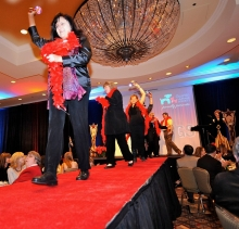 Bid assistants make their entrance down the runway in their red feather boas.